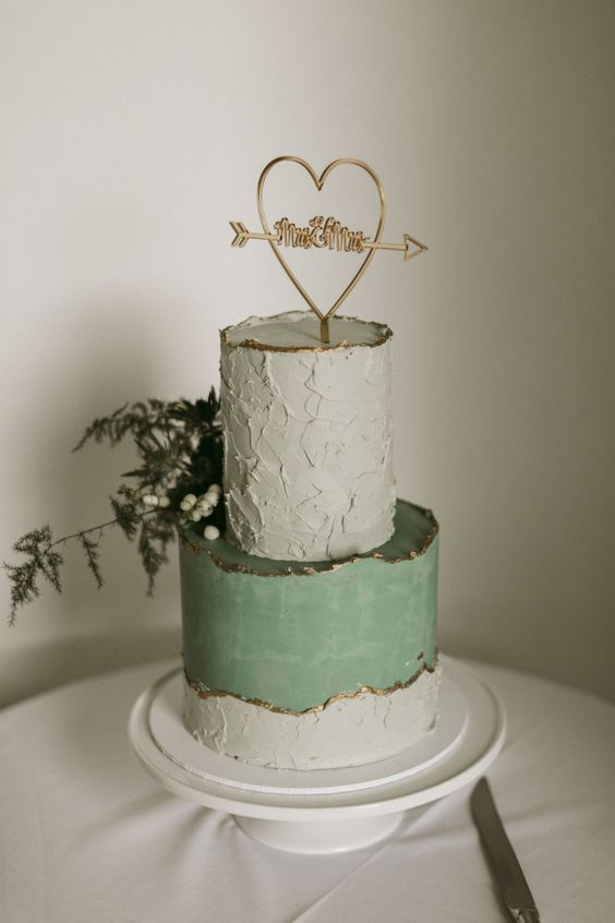 a textural grey and sleek green wedding cake with a gold edge, a gold topper and greenery and berries for a spring wedding