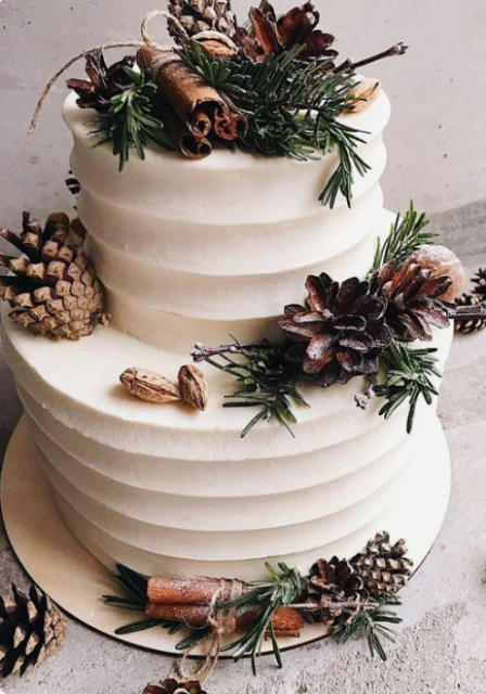 a textural white wedding cake topped with evergreens, nuts and pinecones and cinnamon sticks