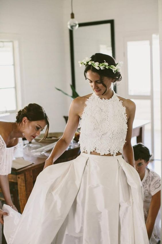a two-piece wedding dress with a lace halter neckline crop top and a pleated skirt with a train for a boho bride