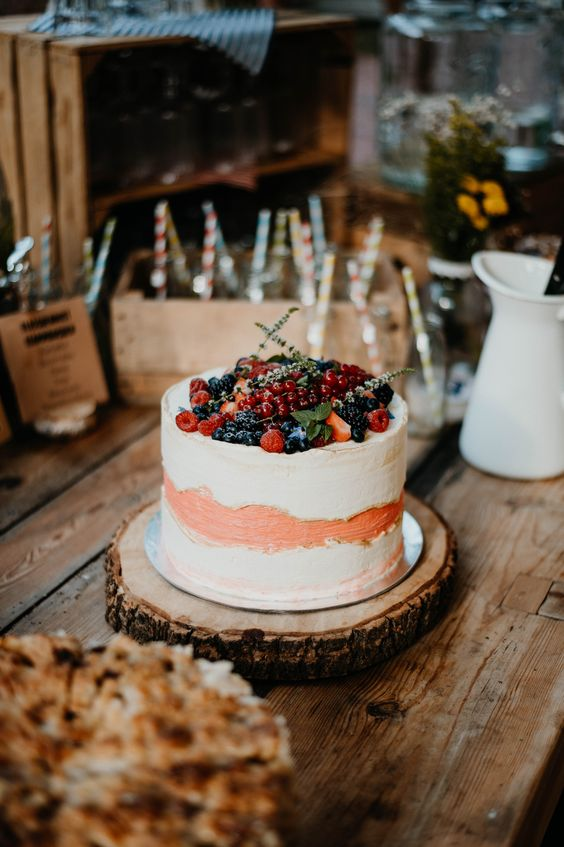 a white and peachy buttercream wedding cake topped with fresh berries and greenery is a lovely wedding dessert