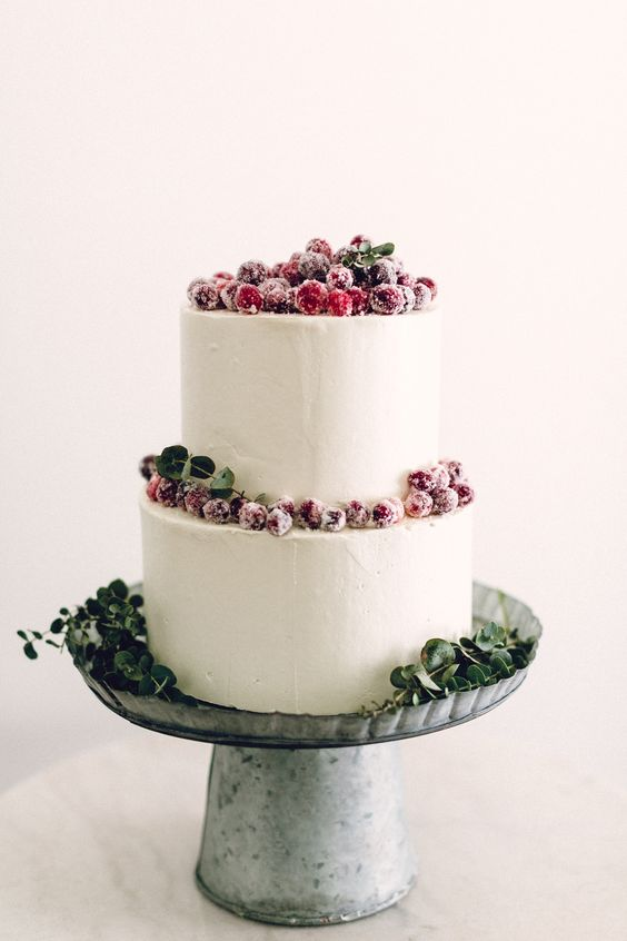 a white buttercream wedding cake decorated with greenery and sugared berries is a stylish idea