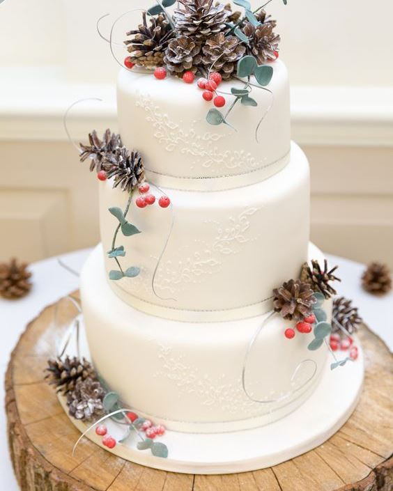 a white patterned wedding cake decorated with pinecones, berries and sugar eucalyptus for a winter wedding