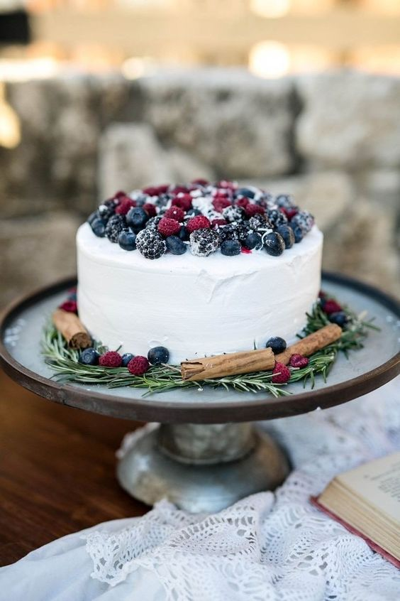 a white textural buttercream wedding cake topped with sugared berries, with cinnamon and rosemary is a cool rustic idea