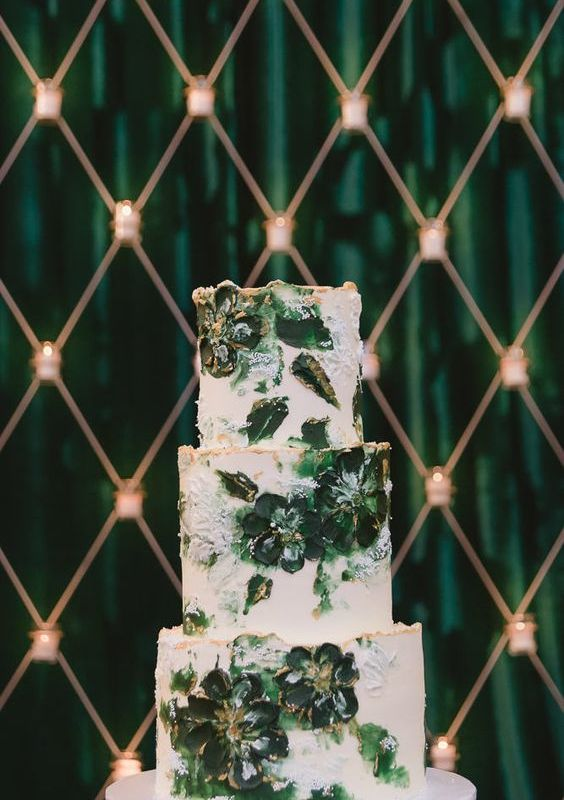 a white textural wedding cake with dark green blooms painted on the tiers, with a gold edge is a very stylish and cool idea