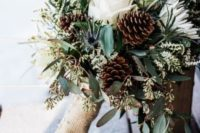 a white wedding bouquet with evergreens, thistles, pinecones and a burlap wrap is very cozy and very cute