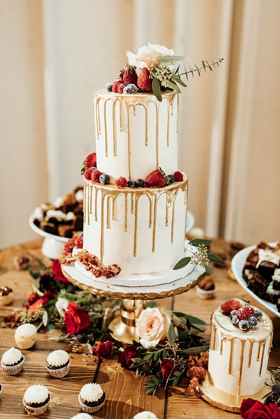a white wedding cake with gold drip, sugared berries, a rose and eucalyptus for a chic winter wedding