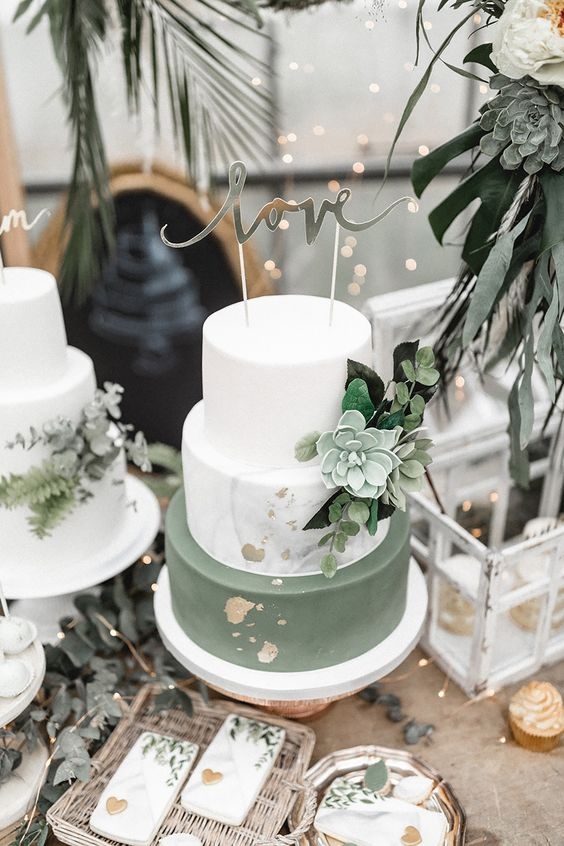 a white, white marble and sleek green wedding cake with gold leaf, a sugar succulent and some greenery plus a calligraphy topper