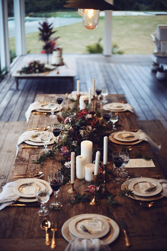 a winter boho lux wedding tablescape with candles, greenery and bold blooms, gold cultery and gold rimmer plates