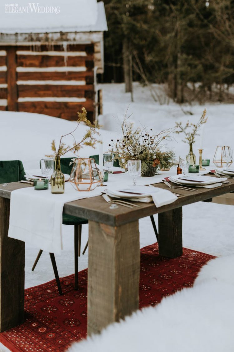 a winter boho wedding table with a white runner, green candleholders and vases, a copper candle lantern and burgundy linens, dried blooms