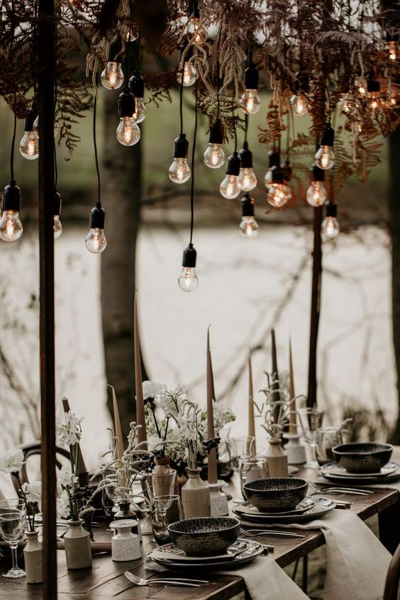 a winter boho wedding tablescape with candles, white blooms and greenery, hanging ferns and bulbs, printed porcelain