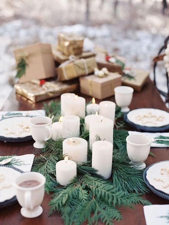 a winter tablescape with an evergrene runner, pillar candles and a stack of gifts on the table