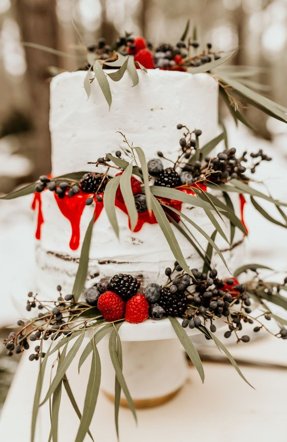 a winter wedding cake decorated with greenery, fresh berries and red drip looks very bold and spectacular