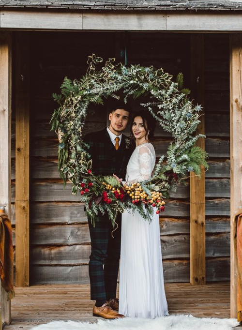 a winter wedding wreath with evergreens, greenery, berries and red blooms for decor and backdrops