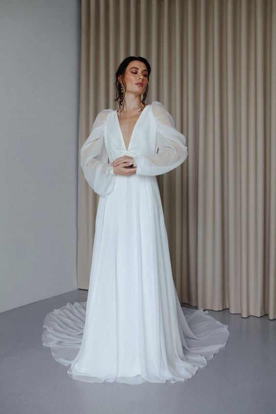 an elegant A-line wedding dress with a pleated skirt with a train, a plunging neckline and illusion sleeves is wow