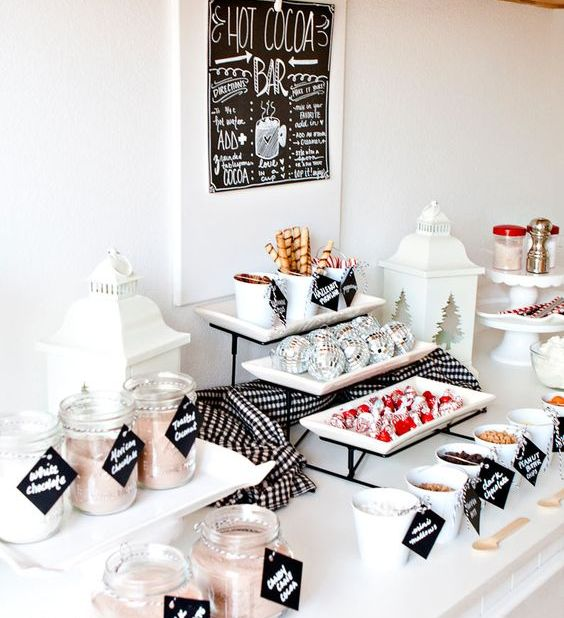 an elegant modern hot cocoa bar in blakc and white, with stands and jars, a sign and candle lanterns