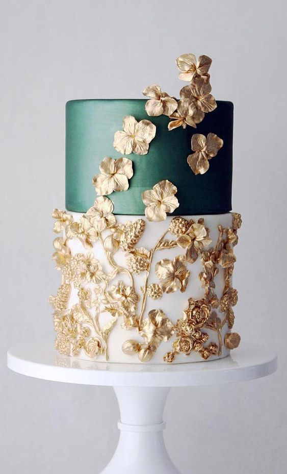 an exquisite wedding cake with a white and dark green tier plus gold sugar blooms and leaves is breathtaking