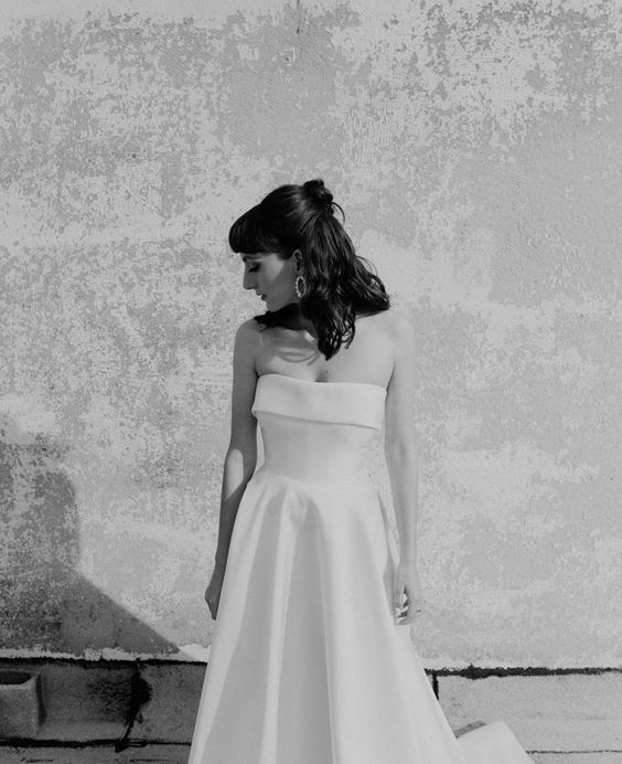 an off the shoulder wedding dress with a pleated skirt for a stylish retro bridal look