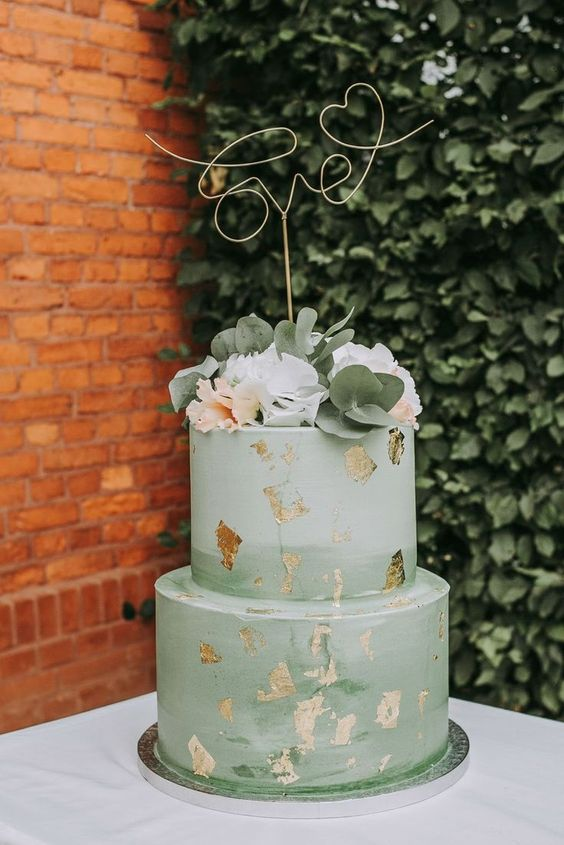 an ombre green wedding cake with gold leaf, white and blush blooms, eucalyptus and a gold calligraphy topper