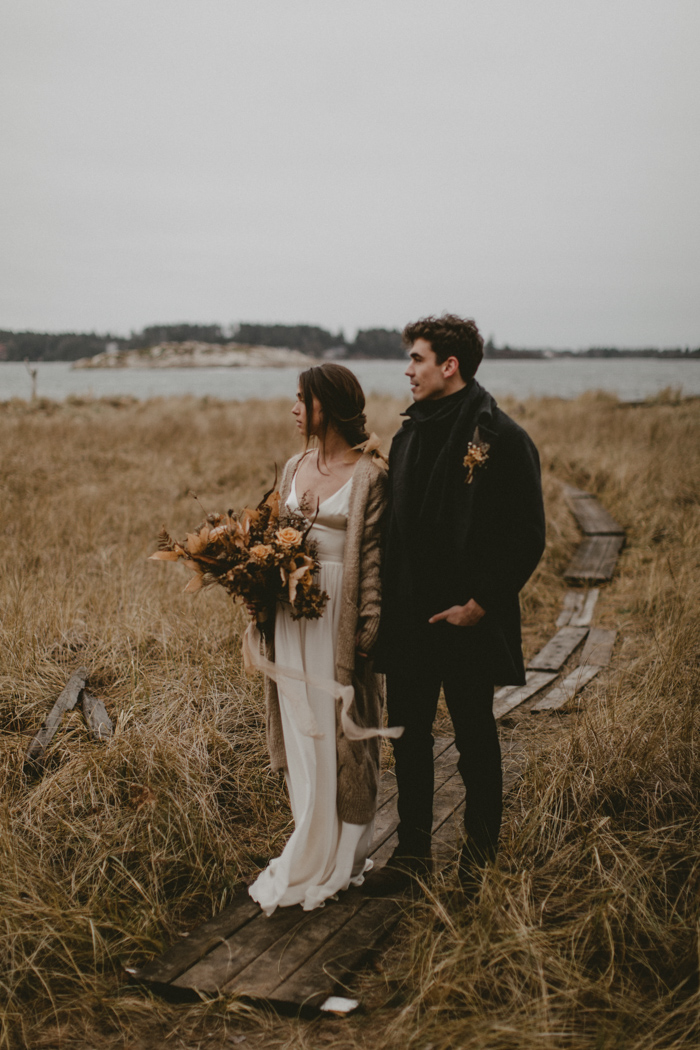 boho winter wedding attire - a silk A-line wedidng dress with a chunky cardigan, a total black look with a coat for the groom