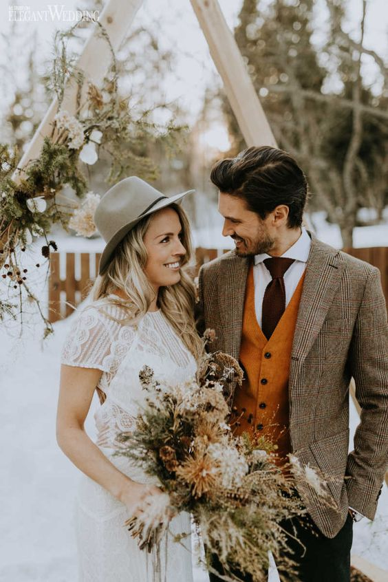 boho winter wedding looks - a boho lace sheath wedding dress plus a hat and a plaid blazer, an orange waistcoat and a brown tie