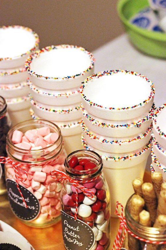 paper cups with srpinkles and candies and sweets in jars are a cool idea for styling your hot cocoa bar