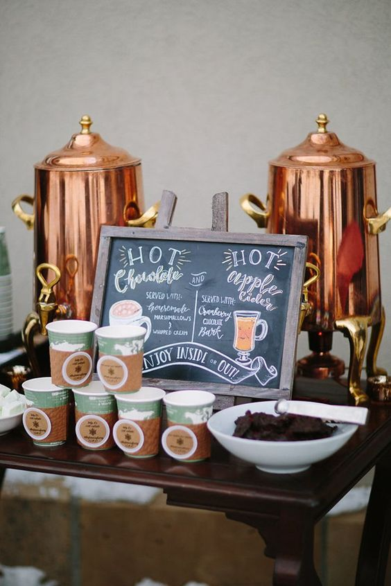 this hot chocolate bar is done with copper tanks, paper cups with tags and holders and a menu sign