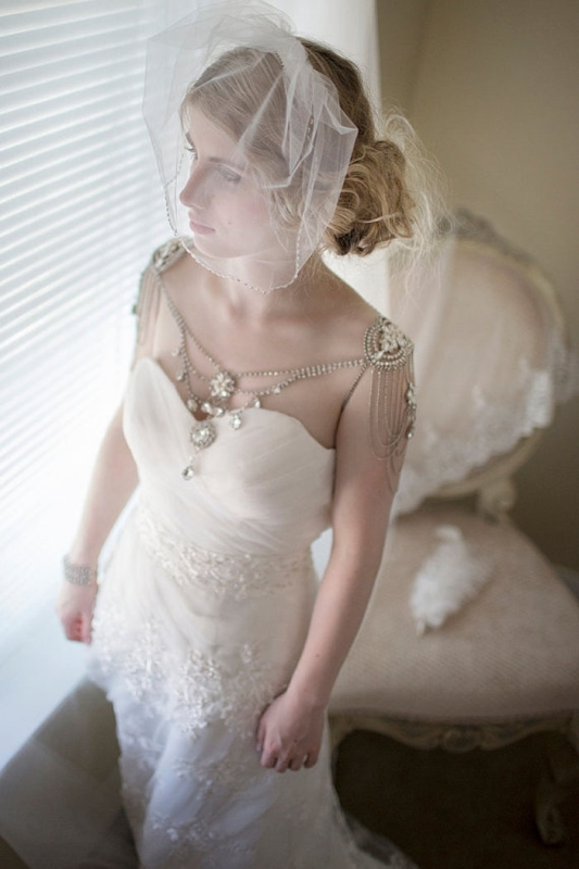 a vintage bridal look with a strapless wedding dress and rhinestone shoulder jewelry plus a low hanging neckline with plenty of rhinestones