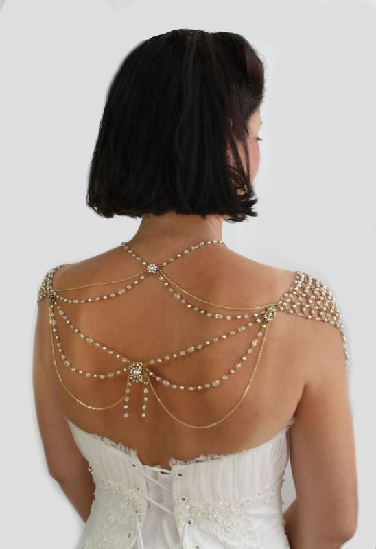 elegant gold and rhinestone jewelry on the shoulders and on the back to accent an open back