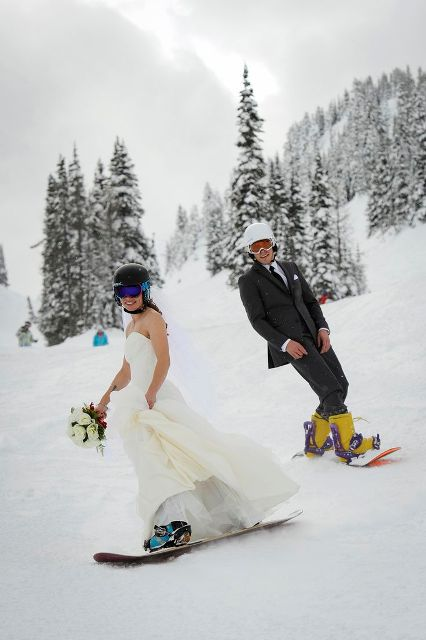 the couple riding snowboards is a cool idea for a wedidng portrait, fun and bold