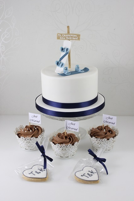 a white wedding cake with navy ribbons and fun cream snowboards on top for a bright look