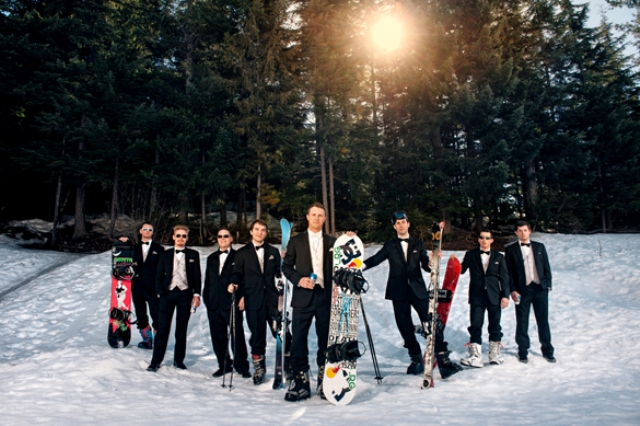 a groom and his groomsmen in black tuxedos and with their colorful snowboards and skis