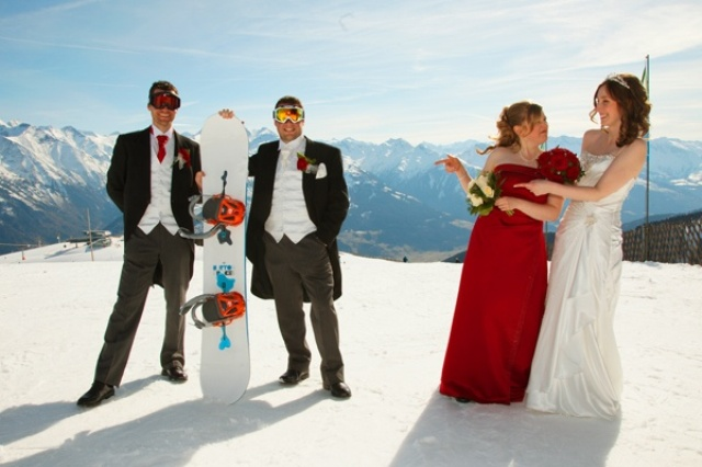 a groom and groomsman wearign morning suits and holding a snowboard and a bride and her bridesmaid next to them