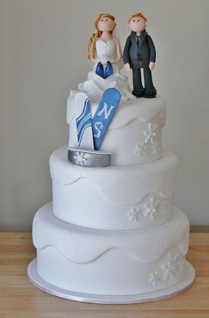 a white wedding cake with fun couple cake toppers and their snwoboards
