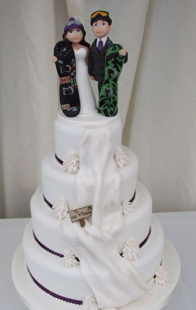 a fun white wedding cake with edible ribbons and black touches plus a fun edible cake topper with snowboards