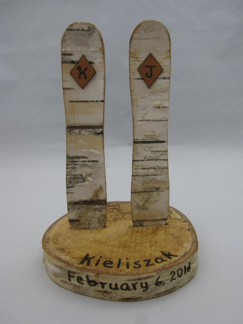 a wedding decoration or favor of a wood slice and wooden snowboards plus the wedding date