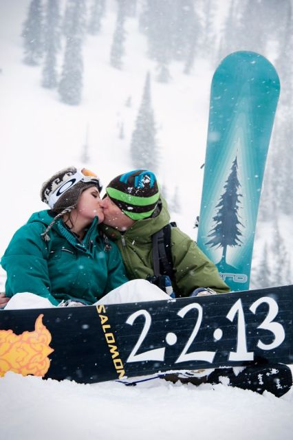a happy couple with their snowboards and wedding date are a nice idea for wedding portraits