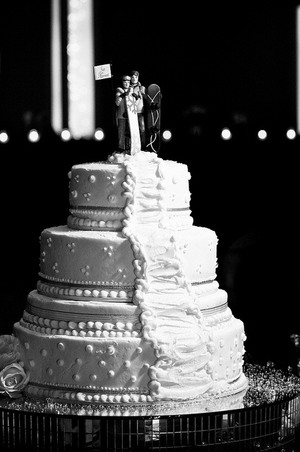 a white textural wedding cake with snowboard toppers is a fun and whimsy idea for a snowboard-loving couple