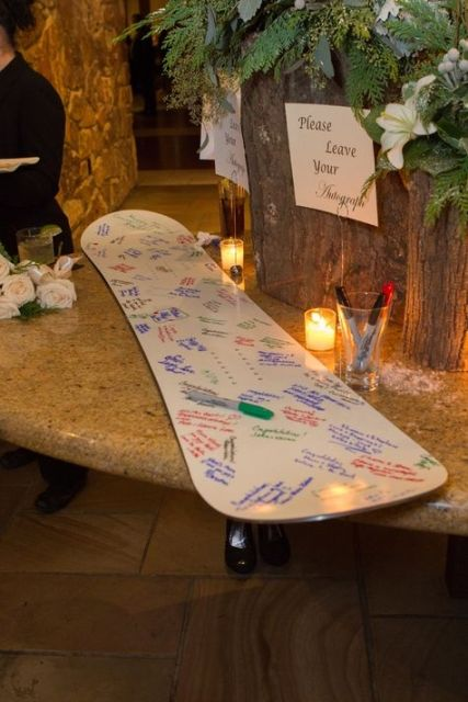 a snowboard instead of a usual wedding guest book is a creative and natural idea for a snowboard wedding