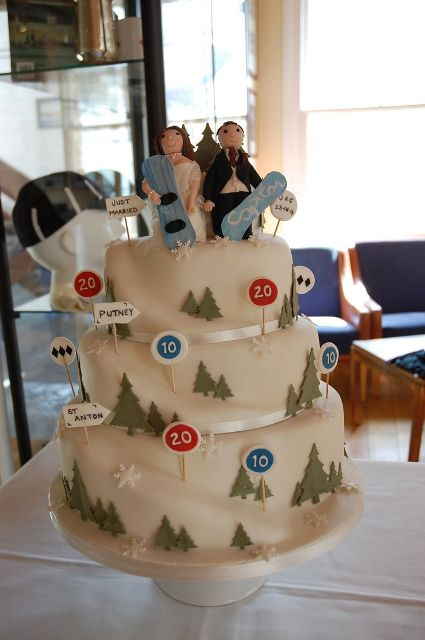 a whimsical wedding cake designed as a snowboard track, with signs, trees and snowboard toppers
