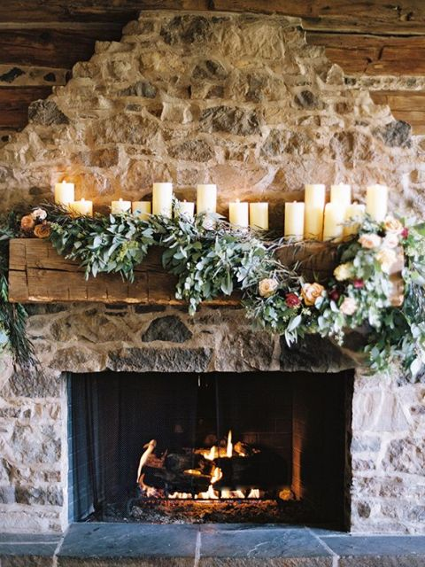 pillar candles on the mantel and lush greenery and blooms make the rough stone fireplace softer