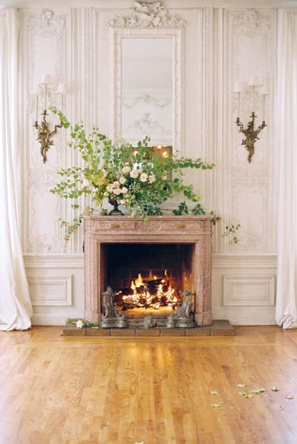 a working fireplace with a lush greenery and floral arrangement in the vase on the mantel looks very elegant