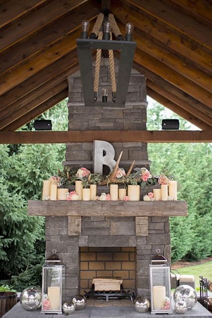 large candles, pink blooms, greenery, antlers, candle lanterns style the rough stone fireplace and make it chic
