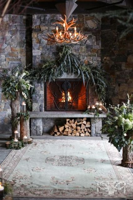 lush greenery, candles in glasses, firewood and greenery and bloom arrangements on tree stumps