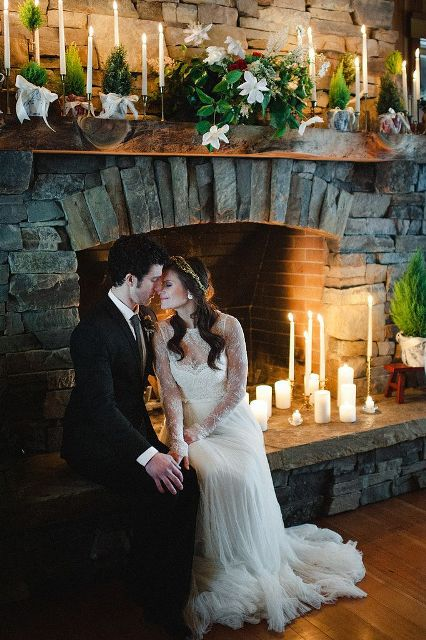 greenery, white blooms, mini trees in pots, candles make the fireplace very stylish and very romantic