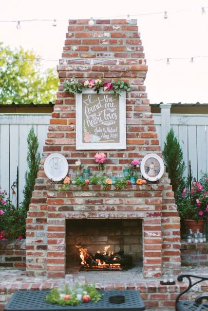 a working fireplace with frames, bright blooms and greenery for a chic and bright look in your wedding lounge