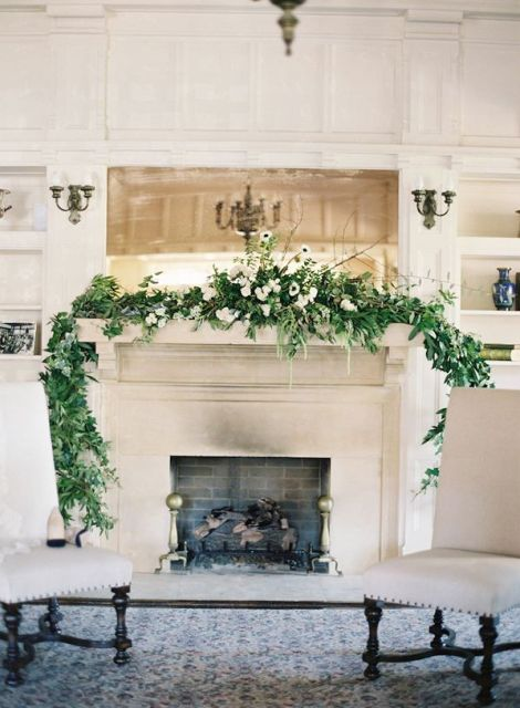 a greenery and white flower wedding garland with twigs is a stylish way to decorate the fireplace