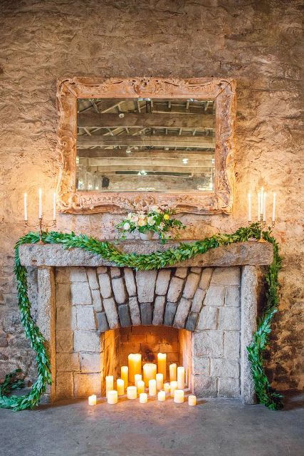 pillar candles in the fireplace, a lush greenery garland and a pastel bloom and greenery arrangement on the mantel