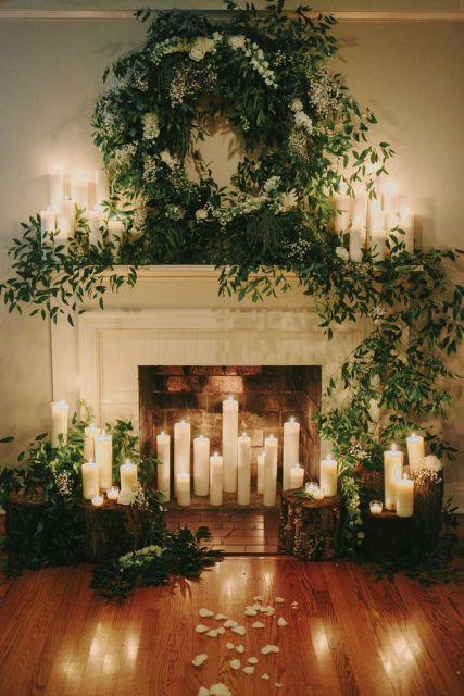 pillar candles on tree stumps and in the fireplace, a greenery and white bloom garland  and a wreath over the mantel