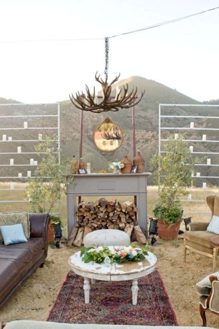 a faux fireplace with firewood, vine wrapped bottles, an antler chandelier for creating an outdoor lounge
