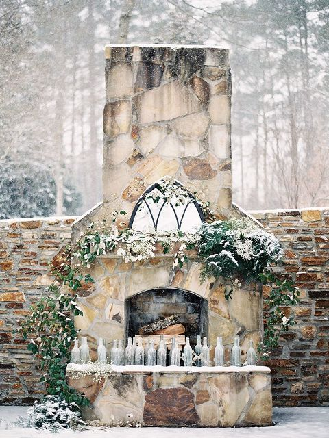 a frozen fireplace with firewood, greenery and bottles that can be used as candleholders